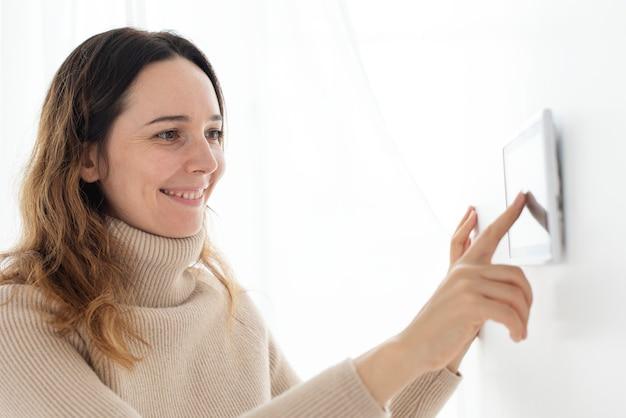 Frau, die auf den monitor des smart home automation panels drückt