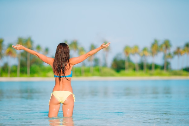 Frau, die auf den strand genießt sommerferien das meer betrachtend legt