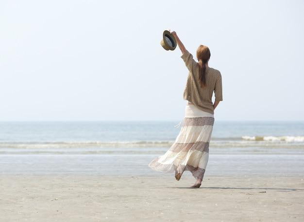 Frau, die auf den strand mit dem arm angehoben geht