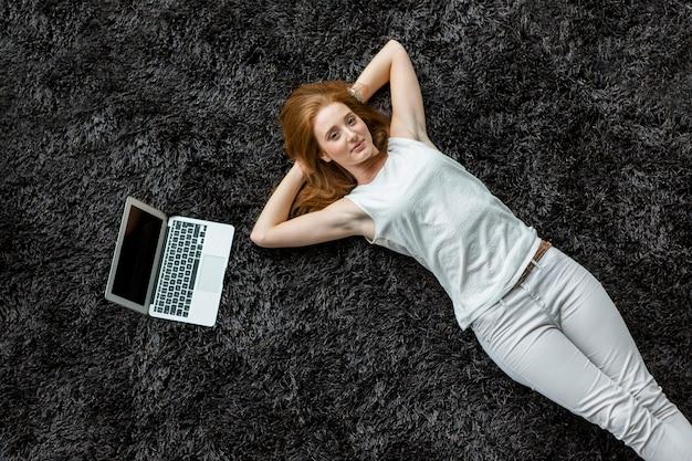 Frau, die auf den teppich legt