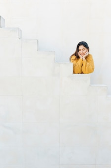 Frau, die auf den weißen schritten weg schauen sich lehnt