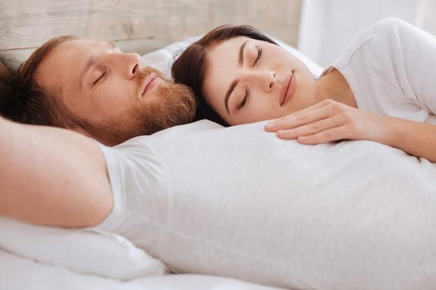 Frau, die auf der brust ihres mannes im bett schläft, während beide nach einem intensiven arbeitstag zu hause entspannen