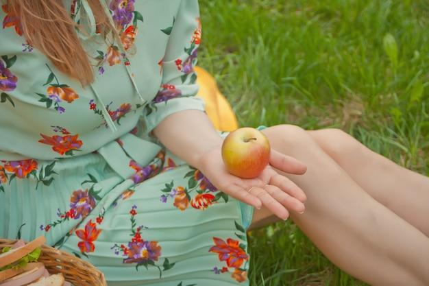 Frau, die auf der gelben abdeckung auf einem grünen gras sitzt und apfel in einer hand hält.