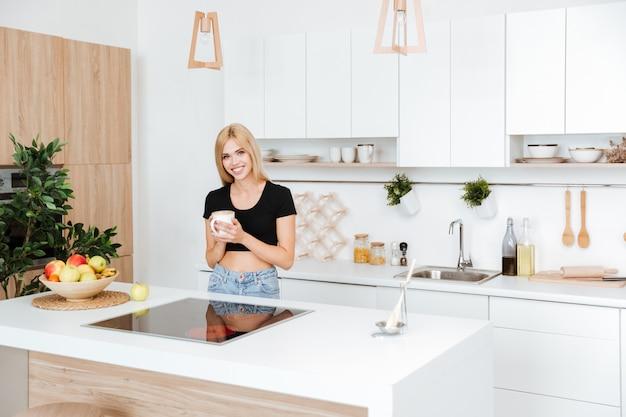Frau, die auf der küche mit warmem tasse kaffee steht