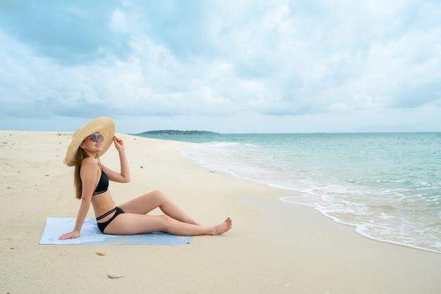 Frau, die auf der küste sitzt, trägt einen bikini, der einen seehut trägt, die umwelt hell und c