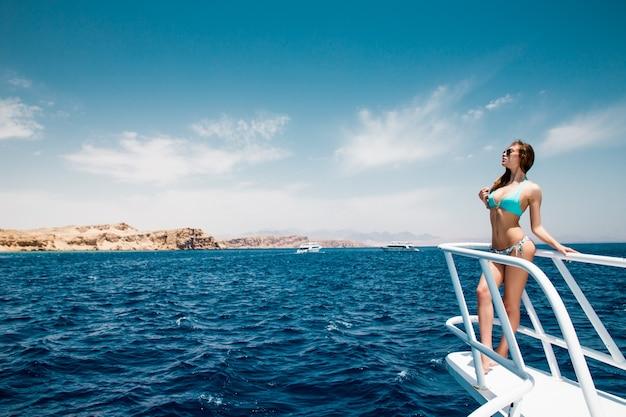 Frau, die auf der nase der yacht an einem sonnigen sommertag steht, brise, die haare entwickelt,
