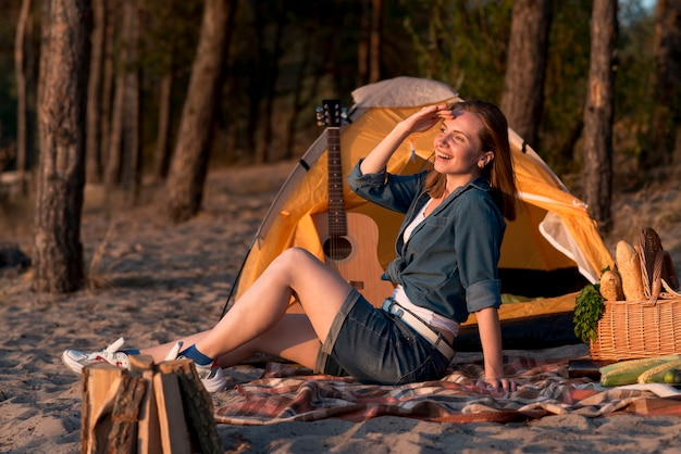 Frau, die auf der picknickdecke weg schaut sitzt
