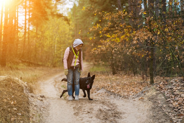 Frau, die auf der straße im wald mit ihrem hund steht