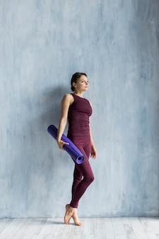 Frau, die auf der wand während ihres yogatrainings stillsteht