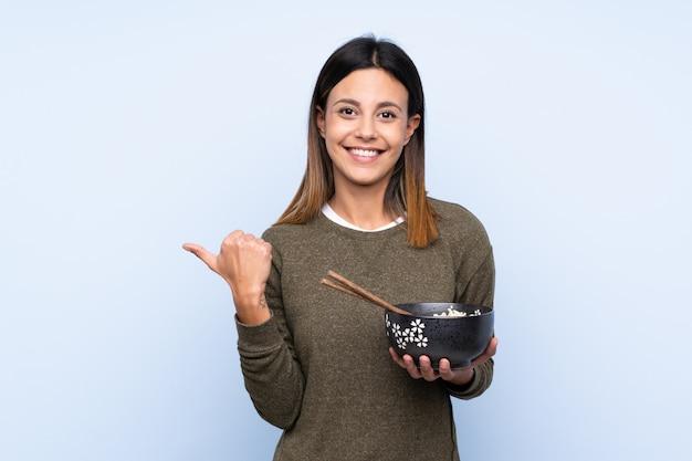 Frau, die auf die seite zeigt, um ein produkt beim halten einer schüssel nudeln mit essstäbchen darzustellen