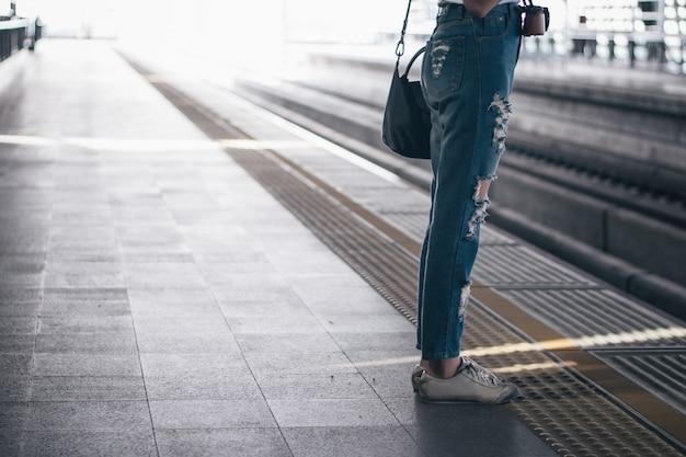 Frau, die auf die stationsplattform wartet und intelligentes telefon an der flughafenverbindungsstation verwendet