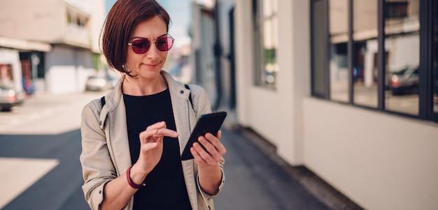 Frau, die auf die straße geht und textmassage am intelligenten telefon schreibt