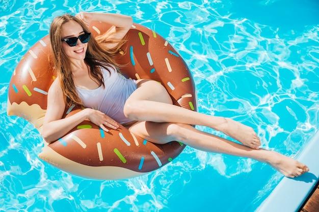 Frau, die auf donutschwimmring lächelt und aufwirft