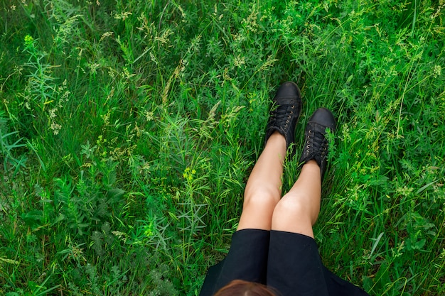 Frau, die auf draufsicht des grünen grases sitzt