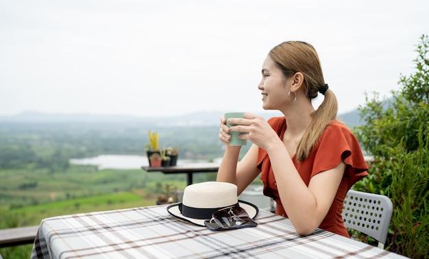 Frau, die auf einem balkon mit natürlichen ansichten sitzt
