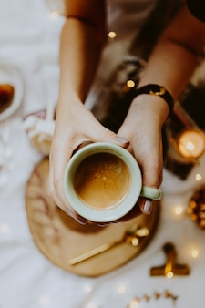 Frau, die auf einem bett sitzt und einen tasse kaffee zeigt