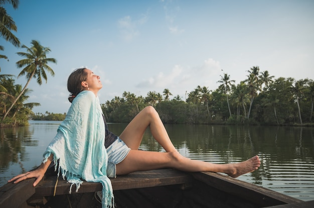 Frau, die auf einem boot in einem tropischen fluss entspannt
