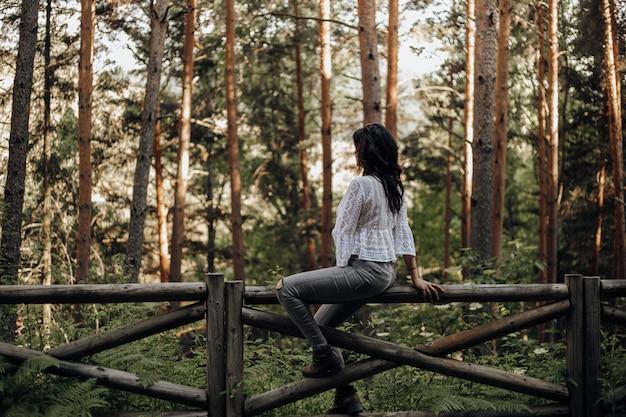 Frau, die auf einem bretterzaun im wald unter den kiefern schauen die natur sitzt