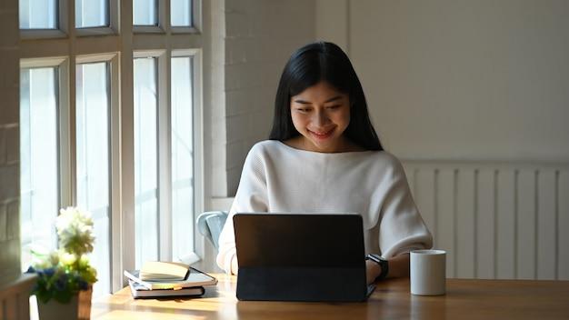 Frau, die auf einem computertablett benutzt / tippt, während sie vor einer topfpflanze und büchern am modernen holztisch mit bequemem wohnzimmer und fenstern als sitzt