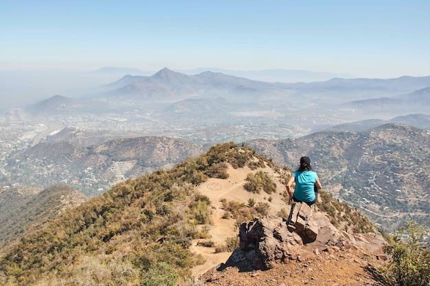 Frau, die auf einem felsen am rande eines berges sitzt, während sie die ansicht genießt