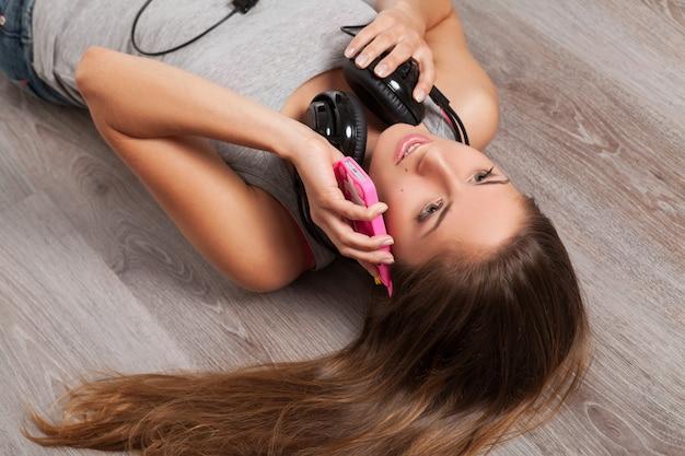 Frau, die auf einem fußboden mit kopfhörern liegt