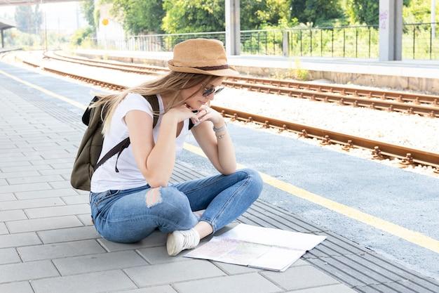Frau, die auf einem fußboden sitzt und eine karte betrachtet