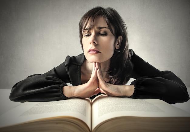 Frau, die auf einem großen buch studiert