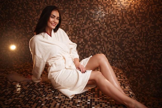 Frau, die auf einem heißen stein im türkischen bad, hamam, sauna sitzt.