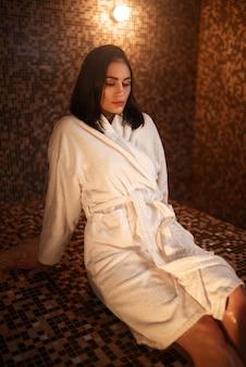 Frau, die auf einem heißen stein in hamam, sauna sitzt