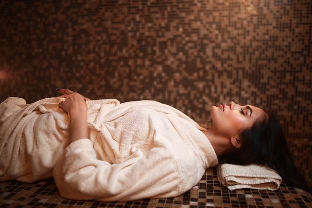 Frau, die auf einem heißen stein, türkischem hamam, sauna liegt