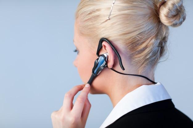 Frau, die auf einem kopfhörer mit fokus auf kopfhörer spricht