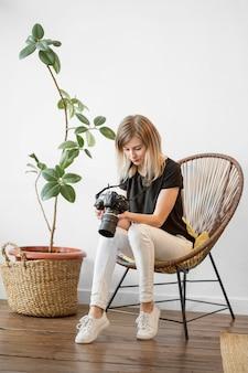 Frau, die auf einem künstlerischen langen schuss des stuhls sitzt