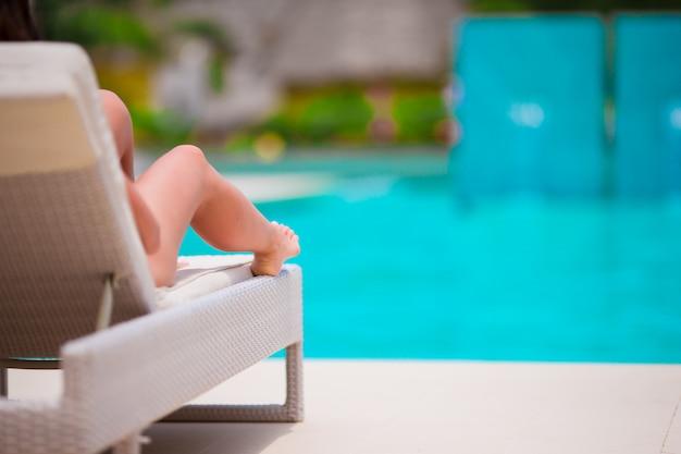 Frau, die auf einem ruhesessel am tropischen erholungsort ein sonnenbad nimmt