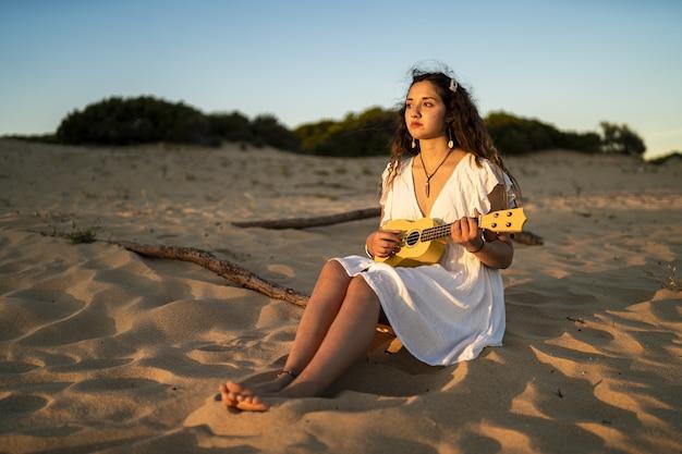 Frau, die auf einem sandigen boden sitzt, während sie eine gelbe ukulele am strand spielt