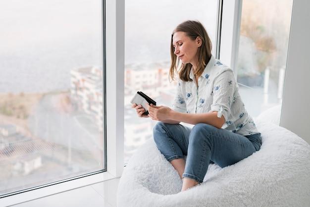 Frau, die auf einem sitzsack mit ihrem telefon sitzt