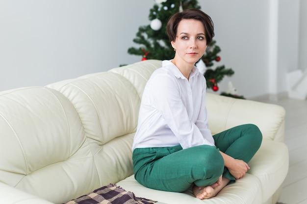 Frau, die auf einem sofa im wohnzimmer mit weihnachtsbaum sitzt