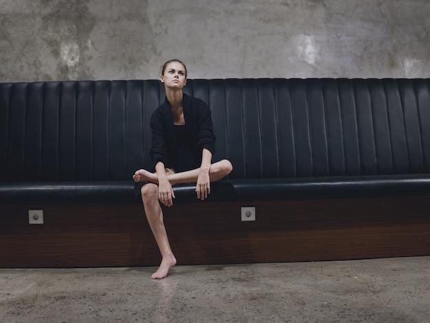 Frau, die auf einem sofa in einem dunklen raum barfuß modell dunkle kleidung sitzt, die auf einen flug auf einer flugzeugreise wartet