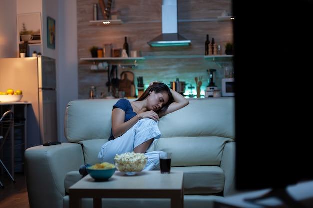 Frau, die auf einem sofa vor dem fernseher schläft, während sie einen gelangweilten film sieht. müde, erschöpfte, einsame, schläfrige dame im schlafanzug, die auf einer gemütlichen couch im wohnzimmer einschläft und nachts die augen schließt
