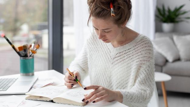 Frau, die auf einem speziellen skizzenbuch zeichnet