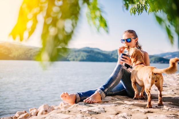 Frau, die auf einem strand mit ihrem hund sitzt und plätzchen isst