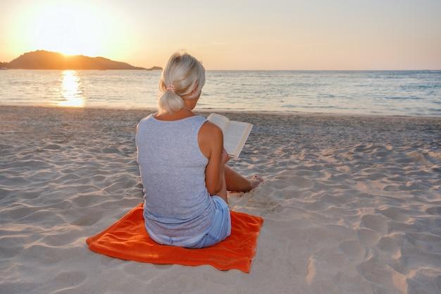Frau, die auf einem strand sitzt und zur sonnenuntergangszeit liest.