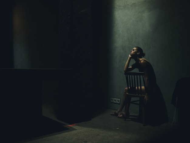 Frau, die auf einem stuhl in einem dunklen raum sitzt, der leichte einsamkeitsgefühle fällt, verärgerte depression