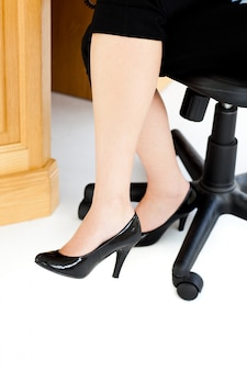 Frau, die auf einem stuhl mit ihren füßen auf dem boden sitzt