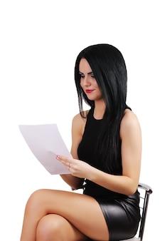Frau, die auf einem stuhl sitzt und eine zeigende weiße karte, isolierten hintergrund hält