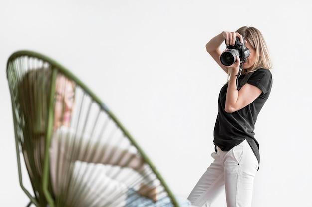 Frau, die auf einem stuhl sitzt und fotografiert wird