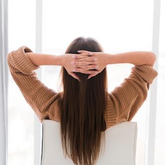 Frau, die auf einem stuhl von hinten ansicht entspannt