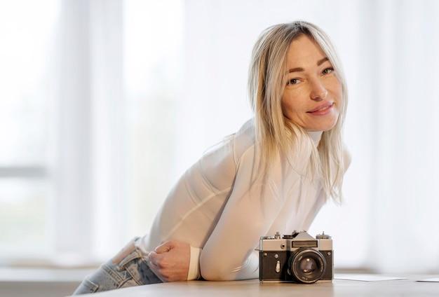 Frau, die auf einem tisch neben einem kamerafoto lehnt