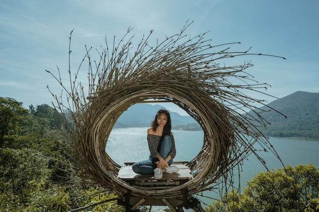 Frau, die auf einem wald oben auf dem berg sitzt
