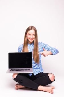 Frau, die auf einen laptop zeigt - lokalisiert über weißer wand
