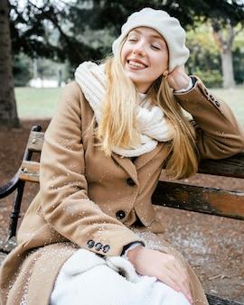 Frau, die auf einer bank am park im winter sitzt